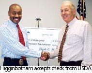 Higginbotham, left, accepts USDA check